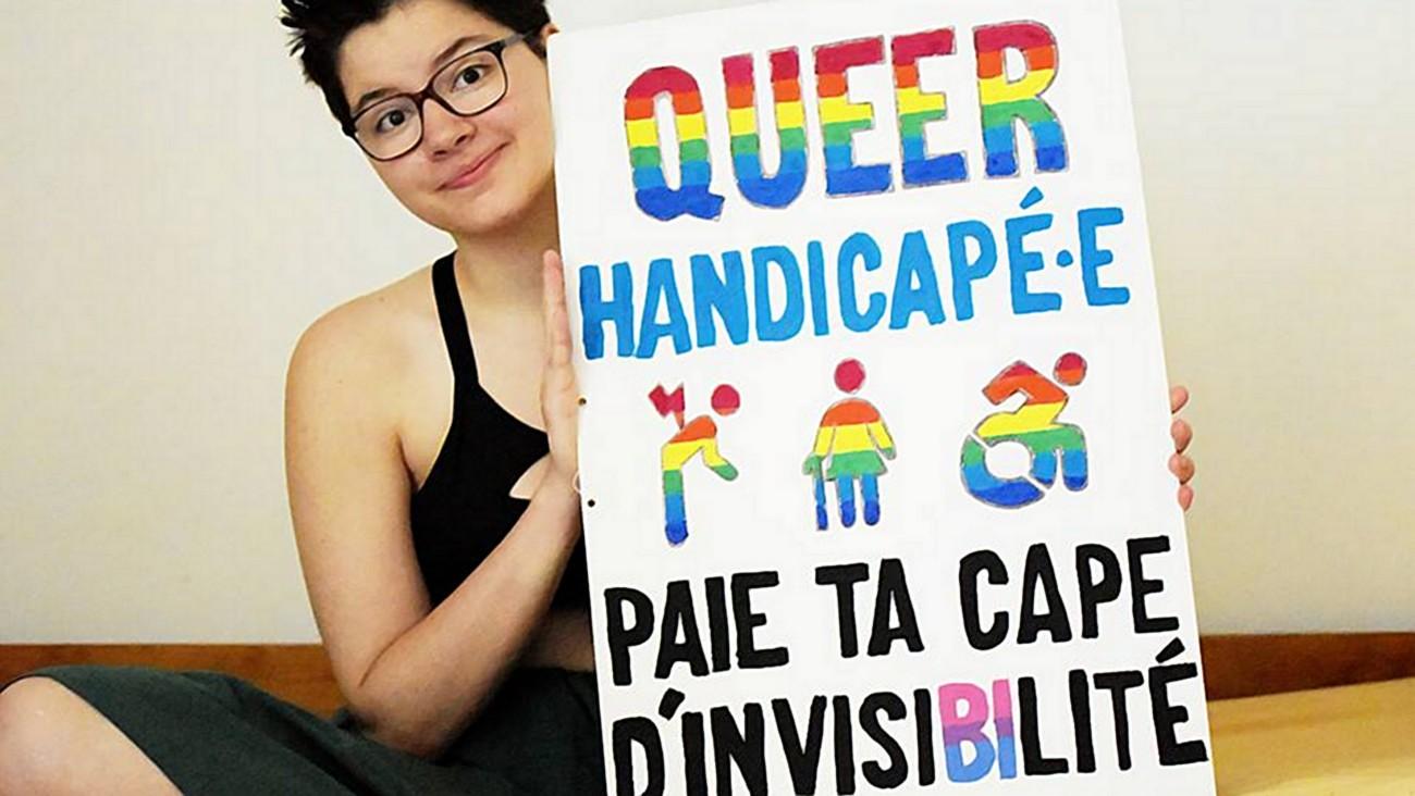 Margot, de « Vivre Avec », tient sa pancarte « Queer handicapé.e paie ta cape d'invisiBIlité », en 2017.