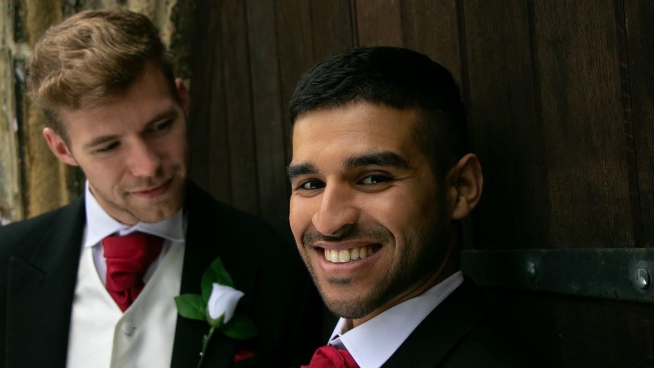 Couple d'hommes, jeunes mariés, devant une église